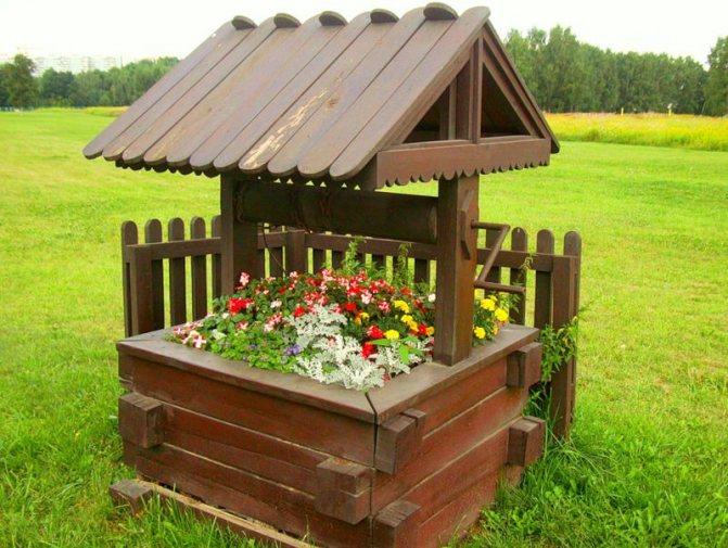 Чаще всего дачные колодцы выполняются из дерева, что очень органично сочетается с садовыми насаждениями и деревянными домовладениями