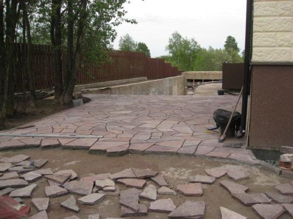 Укладка сланца на бетонную основу вокруг дома.